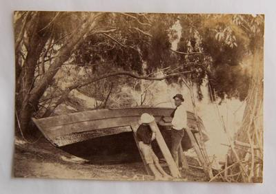Photograph [Man and child repairing a boat]